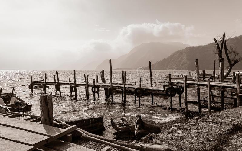 vieux-piliers-en-bois-délabrés-dans-le-lac-atitlan-au-guatemala-en-noir-et-blanc-97208020